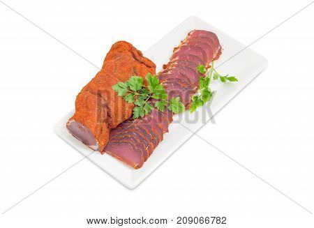 One partly cut piece and one sliced piece of cured pork tenderloin decorated with parsley twigs on a white rectangular dish on a white background