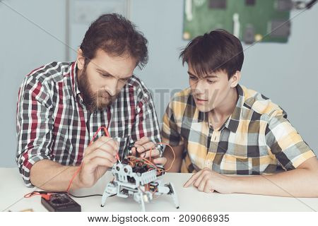 A young guy looks with delight as a man conducts control measurements of the robot's performance. They sit at the table and use a digital multimeter