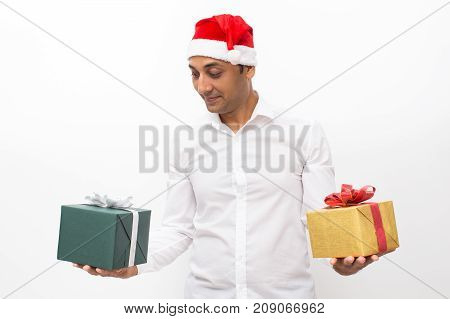 Closeup portrait of content middle-aged handsome man wearing Santa Claus hat, holding two gift boxes and choosing between them. Isolated front view on white background.
