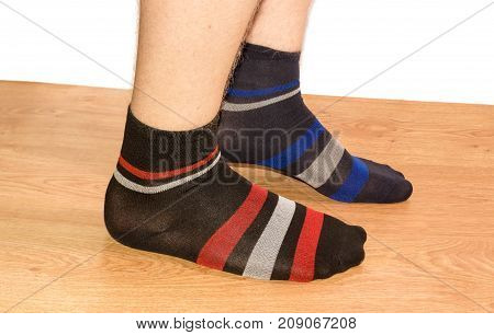 Legs of teenager in different men's socks on a wooden floor on a white background