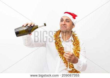 Closeup portrait of content middle-aged handsome man wearing Santa Claus hat, tinsel, holding flute and looking into champagne bottle. Isolated front view on white background.