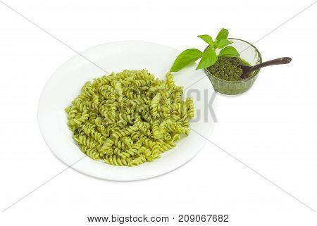Cooked spiral pasta with sauce pesto in the white dish pesto in small glass bowl with small black spoon beside and basil twig on a white background