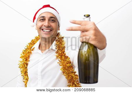 Closeup portrait of smiling middle-aged handsome man wearing Santa Claus hat, tinsel, looking at camera, holding champagne bottle and showing two fingers. Isolated front view on white background.