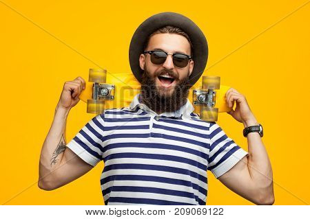 Portrait of young hipster man in stylish outfit posing happily with small yellow longboard on orange background.