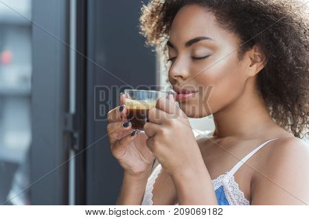 African woman expressing satisfaction while tasting hot beverage in morning