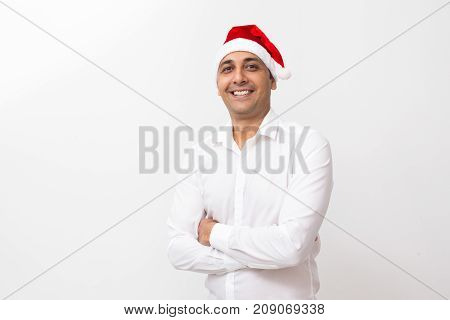 Closeup portrait of smiling middle-aged handsome man wearing Santa Claus hat, looking at camera and standing with his arms crossed. Isolated front view on white background.