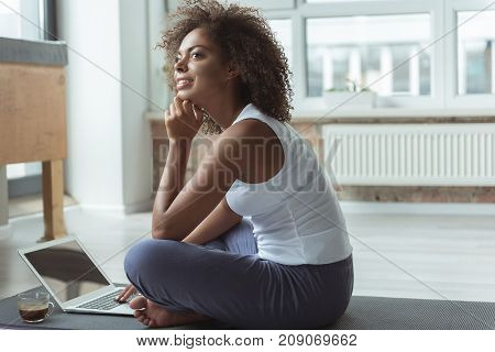 Side view pensive young mulatto girl working on laptop while sitting on mat after exercising in apartment. Copy space