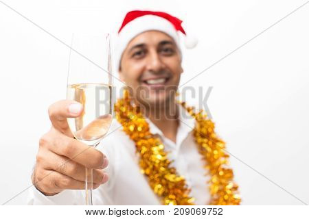 Closeup portrait of smiling middle-aged handsome man wearing Santa Claus hat, tinsel, looking at camera and raising glass with champagne with focus on glass. Isolated front view on white background.