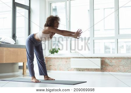 Full length side view happy african girl engaging in sports activities at home. Health concept. Copy space