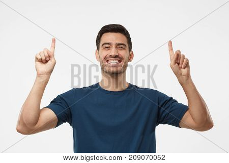 Attractive Young Male In Blue T-shirt Pointing Up With Both Hands Isolated On Gray Background
