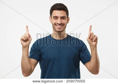 Handsome Male In Blue T-shirt Pointing Up With Two Fingers Isolated On Gray Background