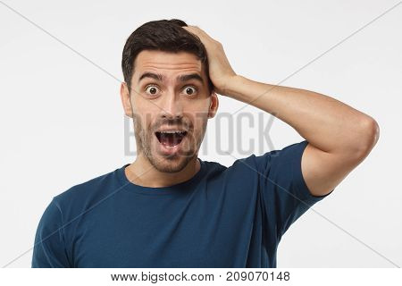 Casual Dressed Young Man In Blue T-shirt Shouting Oh My God With Open Mouth, Surprised By Low Price