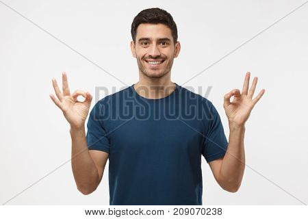 Portrait Of Good Looking Man Isolated On Grey Background Smiling, And Showing Okay Sign With Both Ha