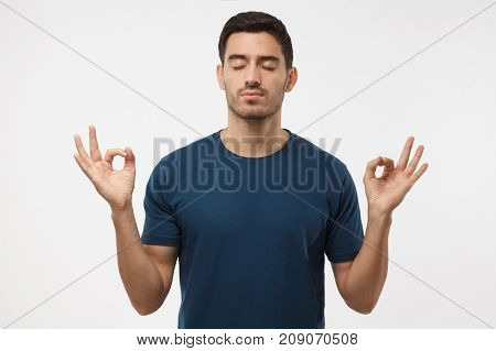 Concentrated Relaxed Man In Blue T-shirt With Closed Eyes, Having Relaxation While Meditating, Tryin