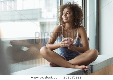 Full length side view outgoing mulatto woman tasting mug of appetizing beverage while looking at street. She locating on cozy sofa. Copy space