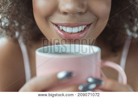 Focus on close up brilliant smile of woman drinking mug of delicious beverage