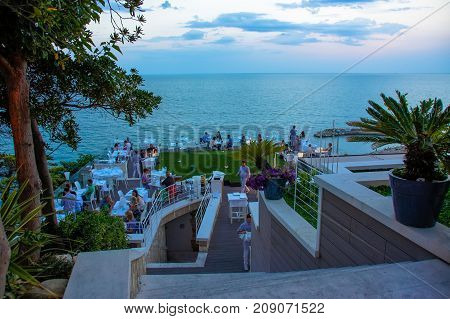 People eat dinner in the restaurant overlooking the sea. The photo was taken in September 2016 in Numana, located on the Adriatic coast in Italy (Marche region). Numana Resort is located in Conero National Park.