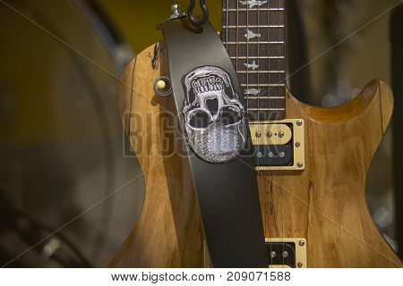 Beautiful detail of an excellent light wood electric guitar with the shoulder strap placed in front with a skull embroidered. The handle and the strings are clearly visible while the background is blurred to focus the attention on the guitar itself.