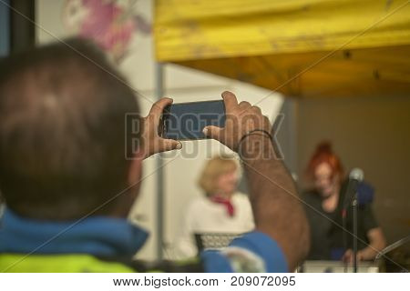 Middle-aged man intending to film a concert with the smartphone an example of a lot of people who lose the best moments of life to show their lives on social networks thus excluded from reality. Mind control from social media.
