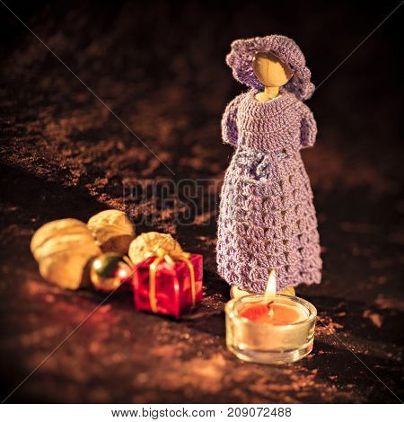 Christmas wood figure with candle and gifts in front of brown background