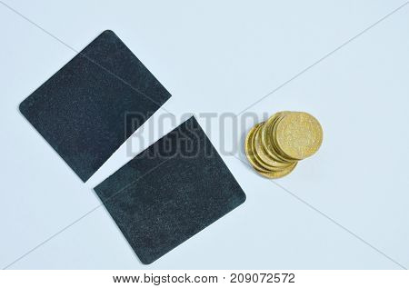 black credit card cutting and cheap golden coins on white background