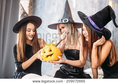 Three Adult Women Carve Halloween Pumpkins While Laughing And Having A Party