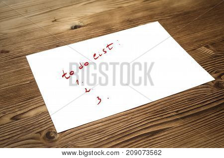 To do list paper page on wooden desk table surface background with copy space.