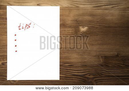 Tips note paper page with copy space on wooden desk table surface background.