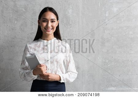 Portrait of cheerful career girl holding electronic tablet in hand. She looking at camera. Copy space. Occupation concept