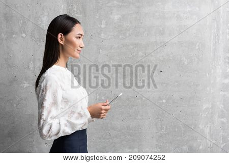 Side view smiling asian businesswoman standing and working with digital device. Copy space. Technology concept
