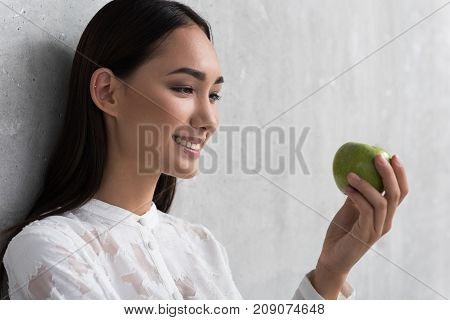 Side view cheerful young woman looking at fresh apple while leaning against concrete wall. Heath meal concept. Copy space