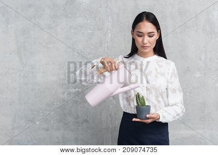 Portrait of calm young asian woman pouring water on cactus in pot. She is standing and holding jar. Copy space in left side