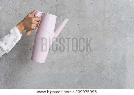 Close up female arm holding modern teapot. Utensil concept. Copy space