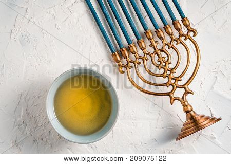 Fragment of Hanukkah with blue candles and butter in a bowl top view horizontal