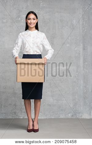Full length portrait of cheerful female keeping big carton in hands. Delivery concept. Copy space