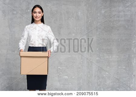 Portrait of smiling asian businesswoman holding cardboard box in arms. Copy space. Job concept