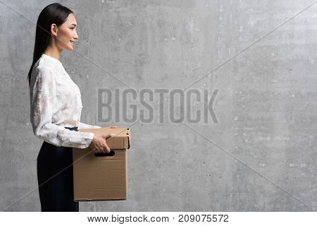 Side view outgoing asian career girl keeping big carton package in hands. Work concept. Copy space