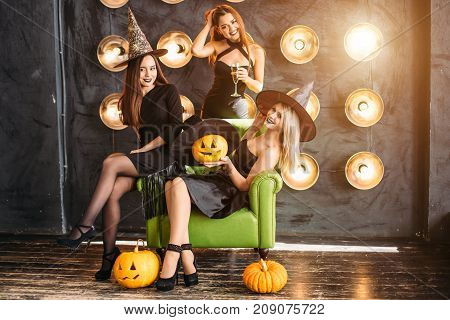 Three Emotional Young Women In Halloween Costumes Having Fun On Party