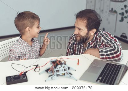 The man severely chastises the boy for spoiling the robot.