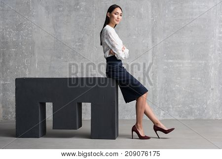 Full length portrait of successful young businesswoman leaning on M shape surface. She is posing and smiling. Lady is looking at camera with confidence. Being over men concept