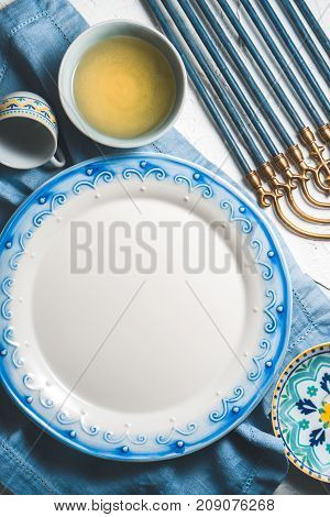 Large plate and olive oil in a bowl, Hanukkah on a table vertical