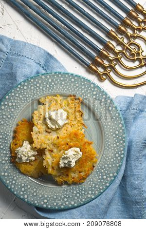 Latkes and curd cheese on a plate, Hanukkah close-up vertical