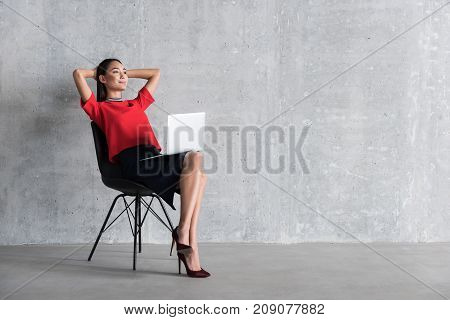 Dreamy woman is sitting at chair and looking ahead with bright smile. Modern open laptop on her legs. Portrait. copy space on right side