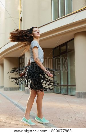 joyful young woman dancing on square, fun girl in a gray T-shirt and a black skirt walking around city