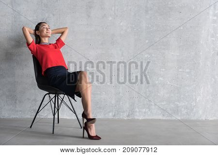 Relaxing lady is sitting on chair and putting hands behind head. She closing her eyes. Copy space on right side