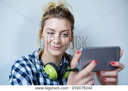 Young woman watching media on cellphone display