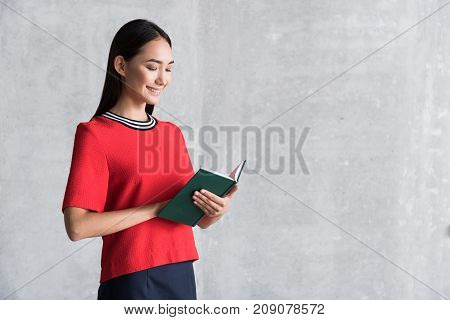 Joyful time. Positive stylish young asian woman is standing with favorite book and reading with pleasure. She is expressing gladness. copy space in the right side