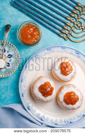 Donuts with jam on a plate and Hanukkah on a turquoise table vertical
