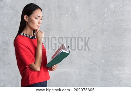 Absorbed in book. Serious elegant charming young asian woman is standing with storybook thoughtfully and touching his chin. copy space in the right side