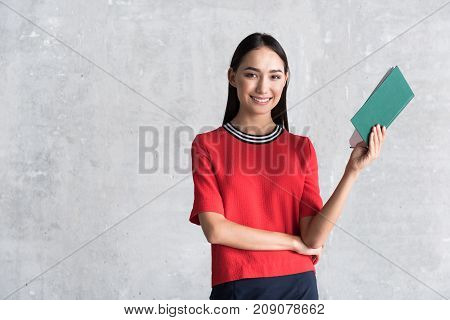 Sharing gladness. Portrait of happy stylish businesswoman is standing with book and looking at camera with joy. copy space in the left side